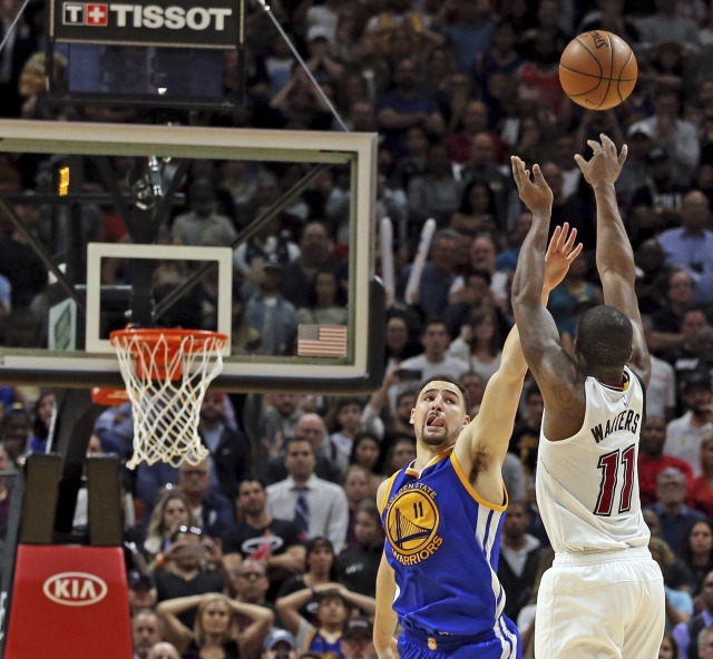 Miami Heat's Dion Waiters shoots a basket in the final seconds of the game to secure a victory over the Golden State Warriors' Klay Thompson during an NBA basketball game in Miami, Monday, Jan. 23, 2017. (Charles Trainor Jr./Miami Herald via AP)